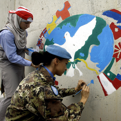 Lebanese children from the neighbourhoods and an Italian peacekeeper (C) paint on a wall of the United Nations Interim Force in Lebanon (UNIFIL) headquarters during the International Day of Peace in the southern Lebanese town of Naqura on September 20, 2013. The United Nations's International Day of Peace is celebrated on September 21 each year to recognize the efforts of those who have worked hard to end conflict and promote peace.    AFP PHOTO MAHMOUD ZAYYAT        (Photo credit should read MAHMOUD ZAYYAT/AFP via Getty Images)